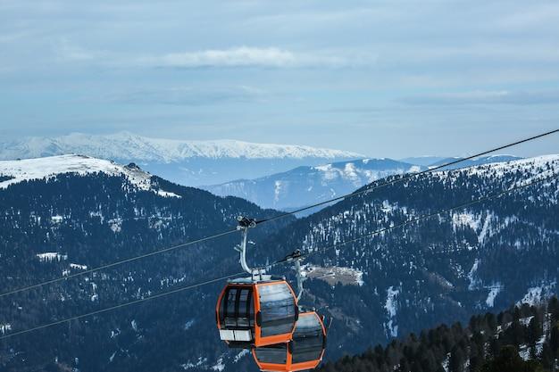 Orange gondelkabinen des kabelbahnaufzugs auf schöner landschaft des schneebedeckten gebirgshintergrundes des winters