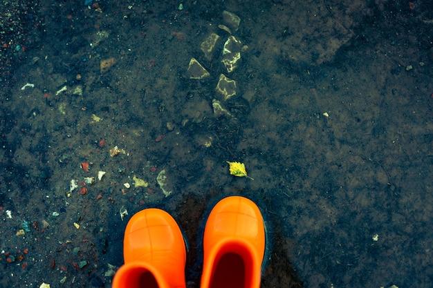 Orange gummistiefel, die in einer pfütze mit gefallenem blatt stehen