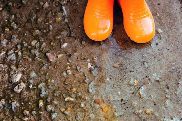 Orange gummistiefel stehen neben der pfütze