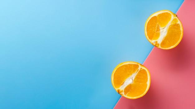 Orange hälften auf farbigem hintergrund