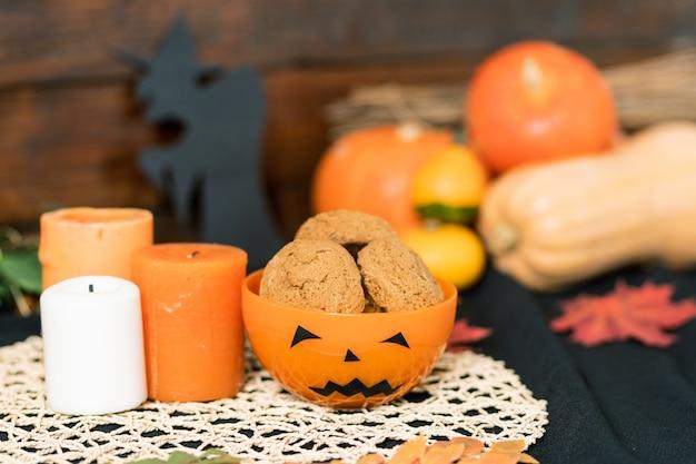 Orange halloween plastikschale mit keksen und drei kerzen auf weißer gestrickter serviette mit kürbissen auf