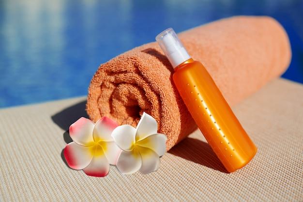 Orange handtuch und sonnencreme körperlotion in einem orangefarbenen rohr