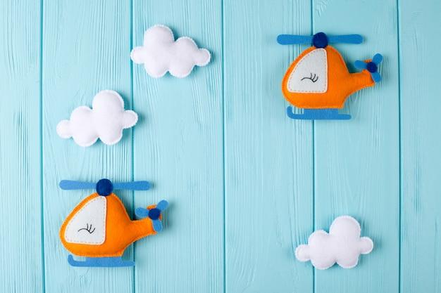 Orange handwerkshubschrauber und -wolken auf blauem hölzernem hintergrund mit copyspace. filz handgefertigte spielzeug.