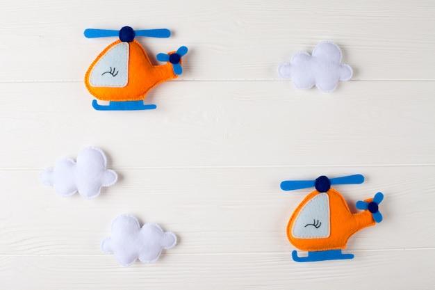 Orange handwerkshubschrauber und -wolken auf weißem hölzernem hintergrund mit copyspace. filz handgefertigte spielzeug.