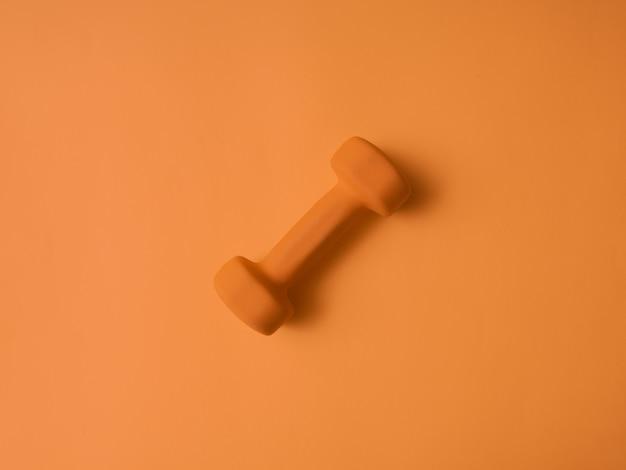 Orange hanteln für fitness auf einem orange hintergrund. minimalismus. platz für text. sportkonzept. flach liegen.