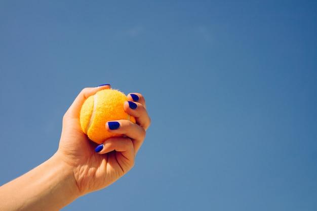 Orange heller tennisball in einer weiblichen hand auf einem hintergrund des blauen himmels