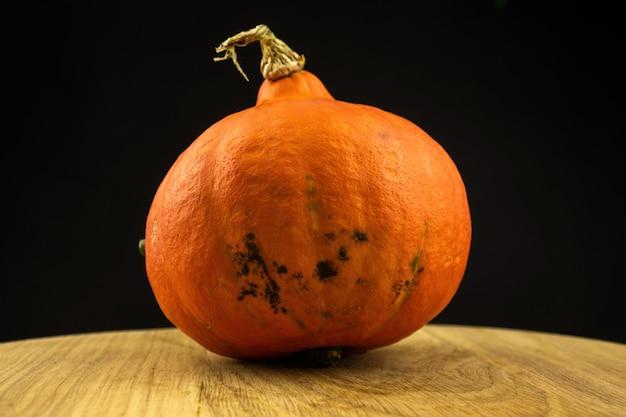 Orange hokkaido-kürbis oder red kuri auf einem holzbrett auf schwarzem hintergrund. frisches gemüselebensmittelkonzeptfoto des herbstes