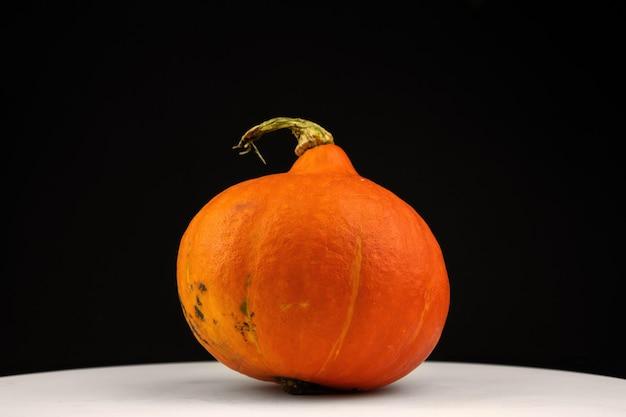Orange hokkaido-kürbis oder red kuri auf schwarzem hintergrund. frisches gemüselebensmittelkonzeptfoto des herbstes