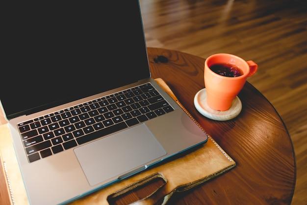 Orange kaffeetasse und laptop auf dem tisch im café.