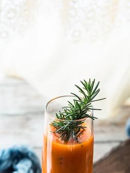 Orange karottensaft auf hölzernem brett