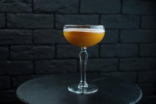 Orange köstlicher süßer cocktail mit tonikum und wodka mit süßem sirup im restaurant auf holztisch über schwarzem hintergrund. original alkoholische cocktails. wochenende an der bar