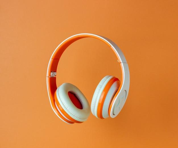 Orange kopfhörer an einer orangefarbenen wand