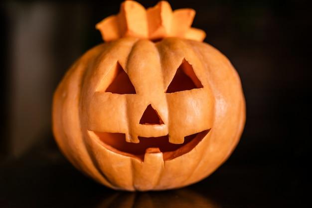 Orange kürbis halloweens mit lustigem gesicht auf dem dunklen hintergrund
