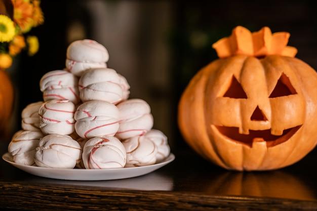 Orange kürbis halloweens mit lustigem gesicht und einer platte von eibischen auf dem dunklen hintergrund. jack-o-laterne auf der feier von halloween