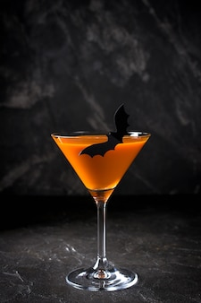 Orange kürbis martini halloween-getränk für party über schwarzem hintergrund mit kopienraum