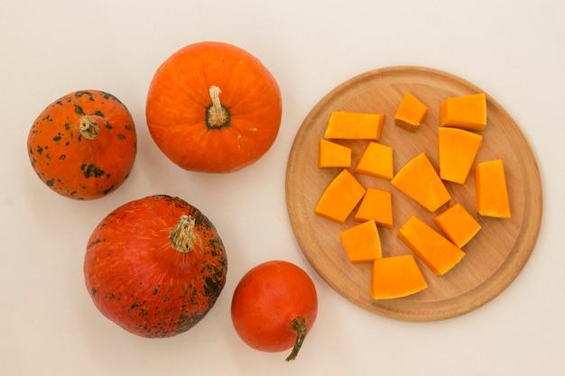 Orange kürbisse auf einer weißen oberfläche und geschnittener kürbis auf einem schneidebrett