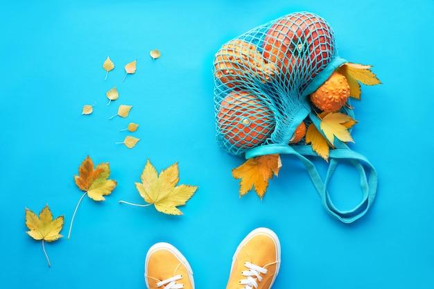 Orange kürbisse im netzbeutel oder im netzbeutel, gelbe ahornblätter und ein paar turnschuhe