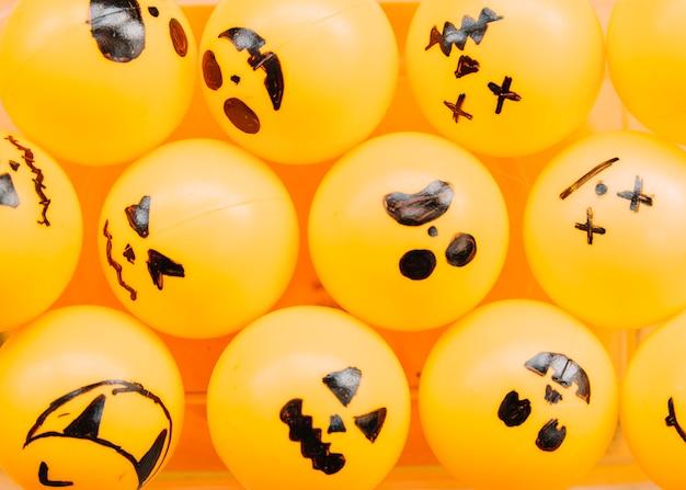 Orange kugeln mit gemalten gruseligen gesichtern