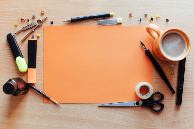 Orange leeres blatt mit vielen briefpapiergegenständen