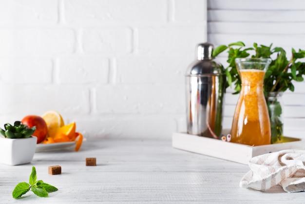 Orange limonade im dekantiergefäß auf einem hölzernen behälter und einem cocktailshaker