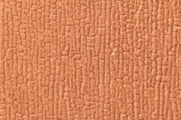 Orange luffy hintergrund des weichen, flauschigen stoffes. beschaffenheit der textilnahaufnahme