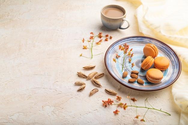 Orange macarons oder macaroons kuchen mit einer tasse kaffee