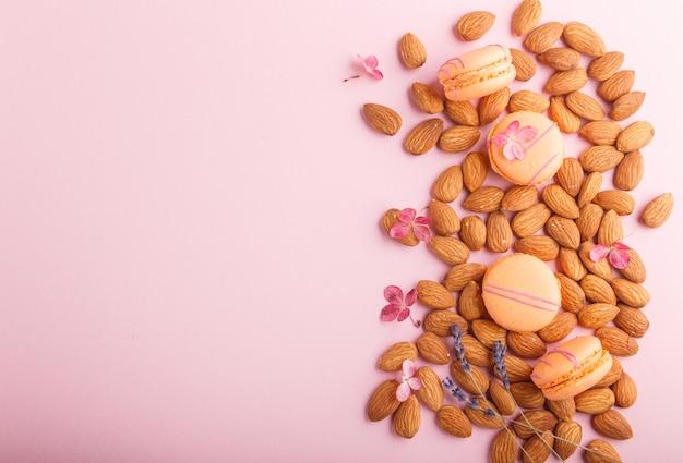 Orange macarons oder macaroons kuchen mit mandelnüssen auf pastellrosa hintergrund. draufsicht, kopierraum.