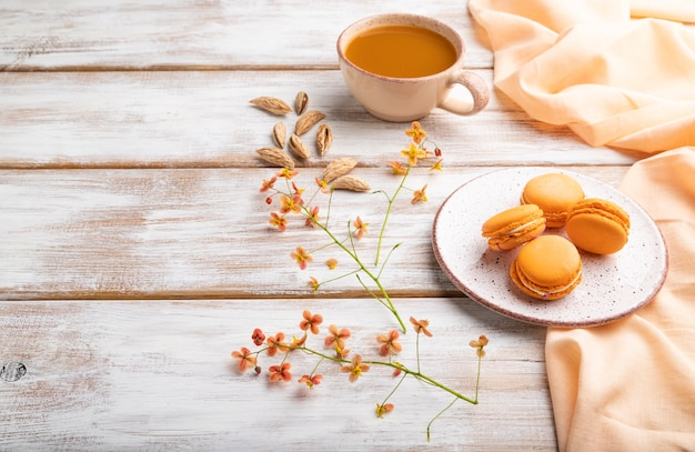 Orange macarons oder macaroons kuchen mit tasse aprikosensaft auf einem weißen holztisch und orange leinen textil. seitenansicht, kopierraum.