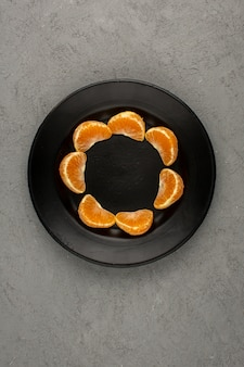 Orange mandarinen in scheiben geschnitten weich saftig reif eine draufsicht in schwarzer platte auf einem grauen schreibtisch