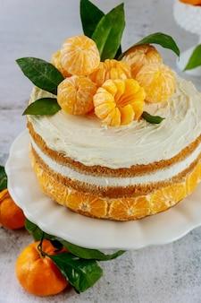 Orange mandarinen mit blättern auf der oberseite des kuchens. nahansicht.