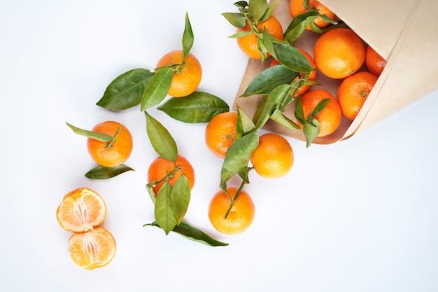 Orange mandarinen mit grünen blättern in einer papiertüte liegen auf einer weißen oberfläche