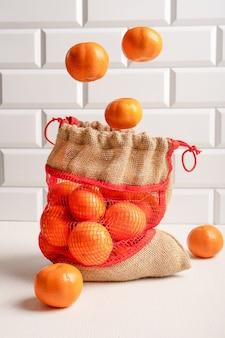 Orange mandarinen schweben über leinwand netzbeutel auf weißem holztisch gegen gekachelte wand