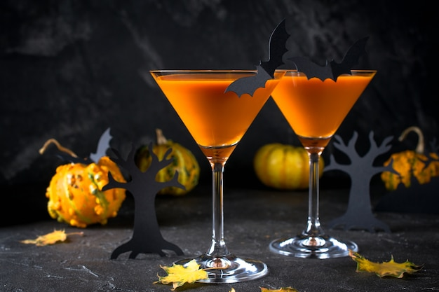 Orange martini cocktails mit fledermäusen und dekor für halloween-party, auf dunklem hintergrund