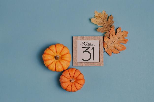 Orange minikürbise und kalenderdatum im holzrahmen