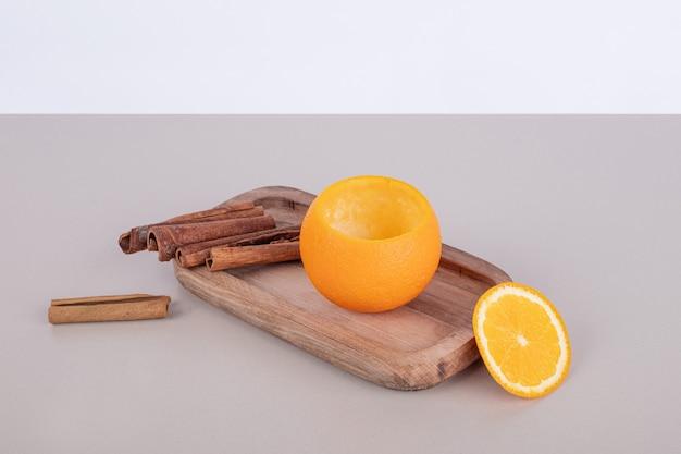 Orange mit zimt auf holzbrett.