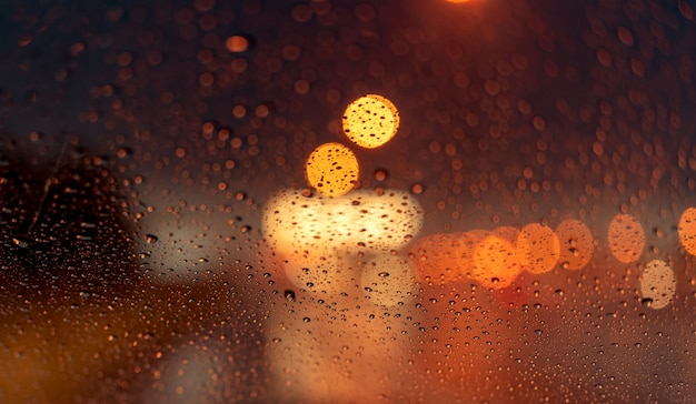 Orange nachtlicht bokeh von straßenlaterne am stau tag. regnerischen tag. transparentes glasfenster mit regentropfen. romantisches wetter. stadt leben.