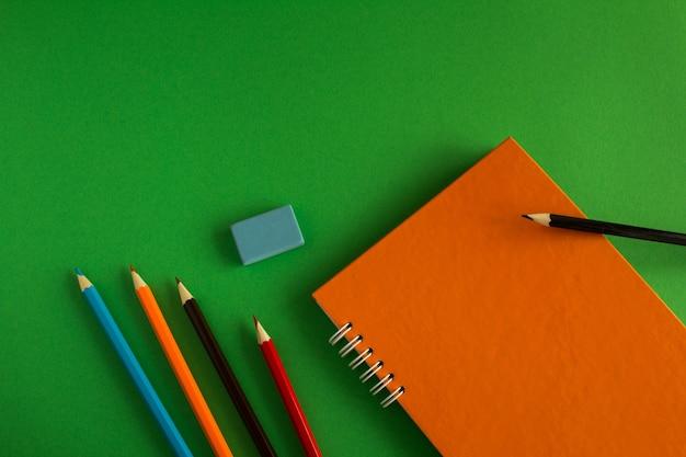 Orange notizbuch und bunte stifte. draufsicht.