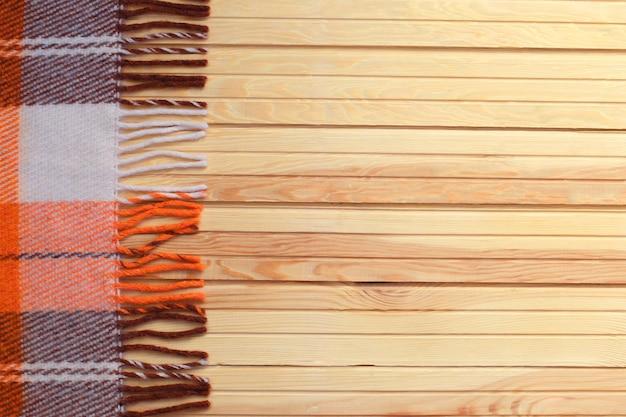 Orange plaid in einem käfig auf einem hölzernen herbsthintergrund