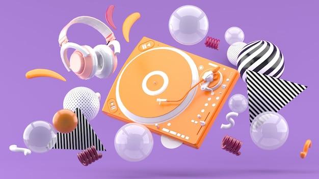 Orange plattenspieler und orange kopfhörer gehören zu den bunten kugeln auf lila. 3d rendern