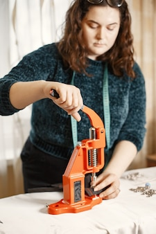 Orange presse für kleidung. knöpfe auf stoff. frau mit nähwerkzeugen