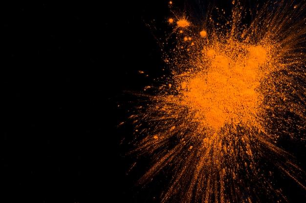 Orange pulverexplosion auf schwarzem hintergrund