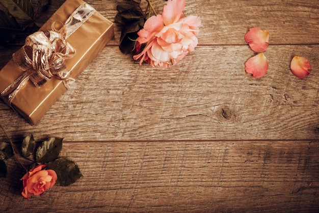 Orange rose der festlichen blumen und geschenkzusammensetzung auf rustikalem hölzernem hintergrund auch im corel abgehobenen betrag. draufsicht von oben, flach. platz kopieren. geburtstag, mutter, valentinstag, frauen, hochzeitstag-konzept. herbststimmung