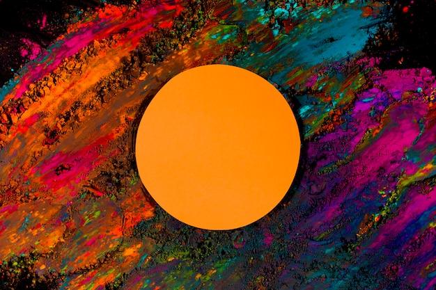 Orange runder rahmen auf buntem holi farbpulver über dem schwarzen hintergrund