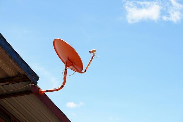 Orange satellitenschüssel zum empfangen von tv-signalen auf dem dach des hauses angebracht um an einem hohen ort zu sein und offen zu sein, um signale gut zu empfangen