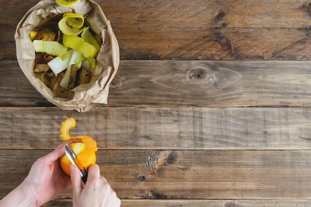 Orange schälen und beutel mit schalen für kompost. rustikaler holzhintergrund.