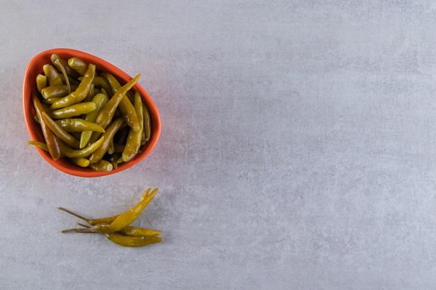 Orange schüssel mit eingelegten chilischoten auf steintisch.