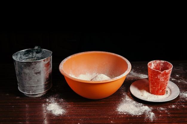 Orange schüssel und mehl auf küchentisch schließen oben