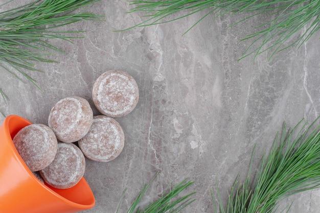 Orange schüssel voll von süßen keksen auf marmoroberfläche.