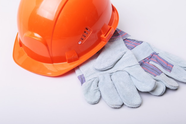 Orange schutzhelm, schutzbrille und schutzhandschuhe auf einem weißen hintergrund.
