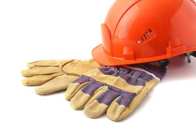 Orange schutzhelm, schutzhandschuhe auf weißer oberfläche.